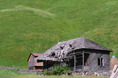 Altes verlassenes Holzhaus mit Hügeln des grünen Grases im Hintergrund Lizenzfreie Stockfotografie