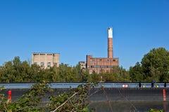 Altes verlassenes Industriegebäude in dem Fluss mit Schiff Lizenzfreie Stockfotografie
