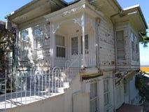 Altes weißes hölzernes Hausäußeres mit zwei Böden lizenzfreie stockbilder