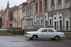 Altes weißes Volga-Auto parkte auf einer cobbled Nebenstraße in Kamianets-Podilskyi Lizenzfreie Stockfotos