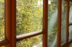 Altes weinendes Fenster mit Sonnenlichtern Stockfoto