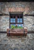 Altes Weinlese-Fenster mit Eisenstangen und Blumen im Topf lizenzfreies stockfoto