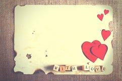 Altes Weinleseblatt papier, zwei rote Herzen, hölzerne Bleistifte und Wörter mit Liebe auf Würfeln auf Leinwand, Sackleinenhinter Lizenzfreie Stockfotografie
