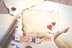 Altes Weinleseblatt papier, zwei rote Herzen, hölzerne Bleistifte und Wörter mit Liebe auf Würfeln auf Leinwand, Sackleinenhinter Stockbilder