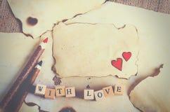 Altes Weinleseblatt papier, zwei rote Herzen, hölzerne Bleistifte und Wörter mit Liebe auf Würfeln auf Leinwand, Sackleinenhinter Stockfoto