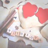 Altes Weinleseblatt papier, zwei rote Herzen, hölzerne Bleistifte und Wörter mit Liebe auf Würfeln auf Leinwand, Sackleinenhinter Stockbild