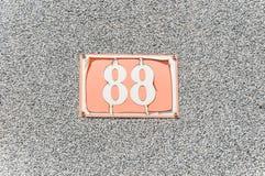 Altes Weinlesehaus-Adreßmetall Nr. 88 achtundachzig auf der Gipsfassade der verlassenen Ausgangsaußenwand auf der Straßenseite Stockfotografie