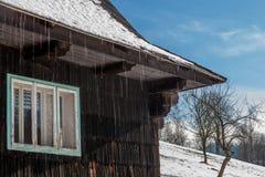 Altes Winterchalet in der Tschechischen Republik mit dem Schneeschmelzen stockbild