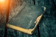 Altes zerlumptes Buch auf einem Holztisch Ablesen durch Kerzenlicht Weinlesezusammensetzung Alte Bibliothek Stockbild