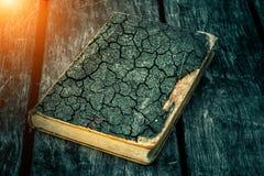 Altes zerlumptes Buch auf einem Holztisch Ablesen durch Kerzenlicht Weinlesezusammensetzung Alte Bibliothek Antike Literatur Lizenzfreies Stockfoto