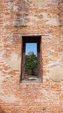 Altes Ziegelsteinfenster mit Natur und altem Ziegelsteintempel außerhalb der Ansicht Lizenzfreies Stockfoto