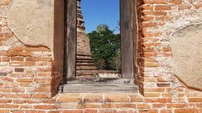 Altes Ziegelsteinfenster mit Natur und altem Ziegelsteintempel außerhalb der Ansicht Stockfotografie