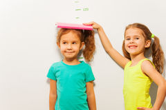 Altezza di misura delle ragazze sulla scala della parete fotografia stock libera da diritti