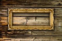 Altgold-Bilderrahmen auf hölzernem Hintergrund Lizenzfreie Stockfotos