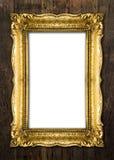 Altgold-Bilderrahmen auf hölzernem Hintergrund Stockfotografie