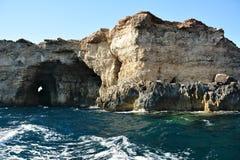 Alti cilfs con le caverne sull'isola di Cominotto immagine stock libera da diritti