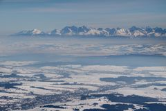 Alti picchi nevosi dentellati di Tatra sopra il bacino nebbioso Polonia di Podhale fotografia stock