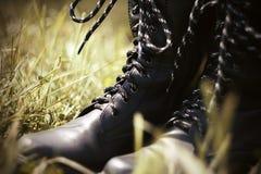 Alti stivali dell'esercito nero che stanno nell'erba immagini stock libere da diritti