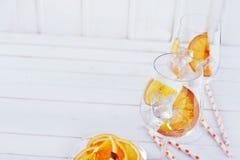 Alti vetri di vino chiave del cocktail ed arancia affettata Fotografia Stock