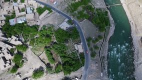altitude haute Rivière avec la route à deux voies avec des véhicules et le village avec les pâturages verts clips vidéos