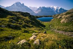 Altitude Mountain Lake and Snowy Peaks on a Sunny Summer Day stock photo