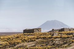 Altitude plain in Peru. Stone buildings and distant volcano mountain on altitude plain in Peru stock photos