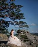 Altmodische Braut sitzt auf den Felsen Stockfotografie