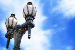 Altmodische Schwarz- und Goldstraßenbeleuchtung gegen blauen Himmel Stockbild