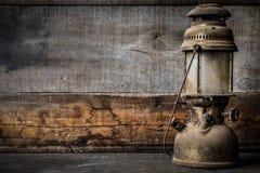 Altmodische Weinlesekerosin-Petroleumlaternelampe, die mit einem weichen Glühenlicht mit gealtertem Bretterboden brennt Stockfoto