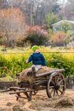 Altmodischer kleiner Junge, der an einem hölzernen Wagen der Weinlese sitzt lizenzfreie stockbilder