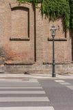 Altmodischer Laternenpfahl vor altem Backsteinbau Stockbilder