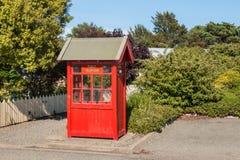 Altmodischer roter Garten der Telefonzelle öffentlich Lizenzfreie Stockfotos
