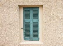Altmodisches abgenutztes Fenster mit den grünen hölzernen Fensterläden, geschlossen, auf vergipstem Wandhintergrund stockfotos