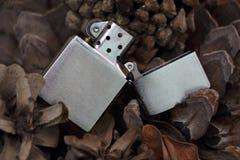 Altmodisches Feuerzeug auf Hintergrund von Kiefernkegeln Stockfoto