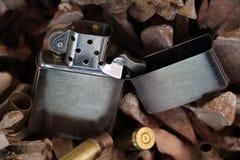 Altmodisches Feuerzeug auf Hintergrund von Kiefernkegeln Lizenzfreies Stockbild