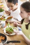 Alto ángulo de los niños que comen verduras en la escuela imagen de archivo libre de regalías