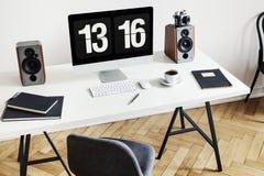 Alto ángulo de un escritorio con un ordenador, los cuadernos, los altavoces y el teclado al lado de una silla en un interior de M imagenes de archivo