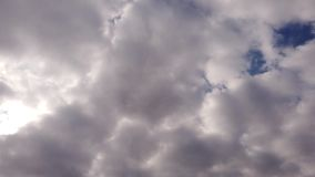 Alto cumulus clouds in time lapse with white light effects blowing in the sky. Alto cumulus flying clouds in time lapse -  banks of softly gray clouds stock video