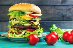 Alto de lujo del cheeseburger grande en fondo de madera verde Imagen de archivo libre de regalías