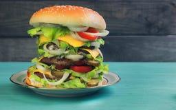Alto de lujo del cheeseburger grande en fondo de madera verde Imagen de archivo