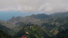 Alto del fuerte viento en las montañas, vista aérea del valle y pequeños pueblos en la cordillera almacen de video