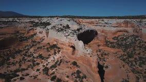 Alto del vuelo del abejón alrededor de la formación de roca increíble de los arcos con los turistas dentro de las montañas asombr metrajes