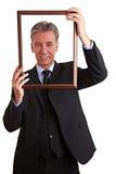 Alto directivo que lleva a cabo el marco vacío Imagen de archivo libre de regalías