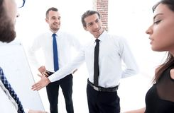 Alto diretivo de apontar a equipe do negócio em um flipchart vazio imagem de stock royalty free