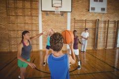 Alto escolar alrededor para tomar un tiro de pena mientras que juega a baloncesto Imagenes de archivo