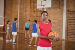 Alto escolar que lleva a cabo un baloncesto mientras que equipo que juega en fondo Foto de archivo libre de regalías