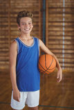 Alto escolar sonriente que lleva a cabo un baloncesto en la corte Fotografía de archivo