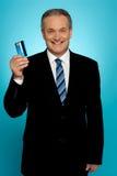Alto executivo que mostra o cartão de crédito Fotografia de Stock