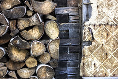 Alto fondo della legna da ardere di struttura con la parete ed il giallo della casa dell'azienda agricola Fotografie Stock