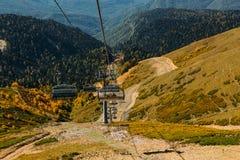 Alto funicular en las montañas sobre el bosque del otoño fotos de archivo